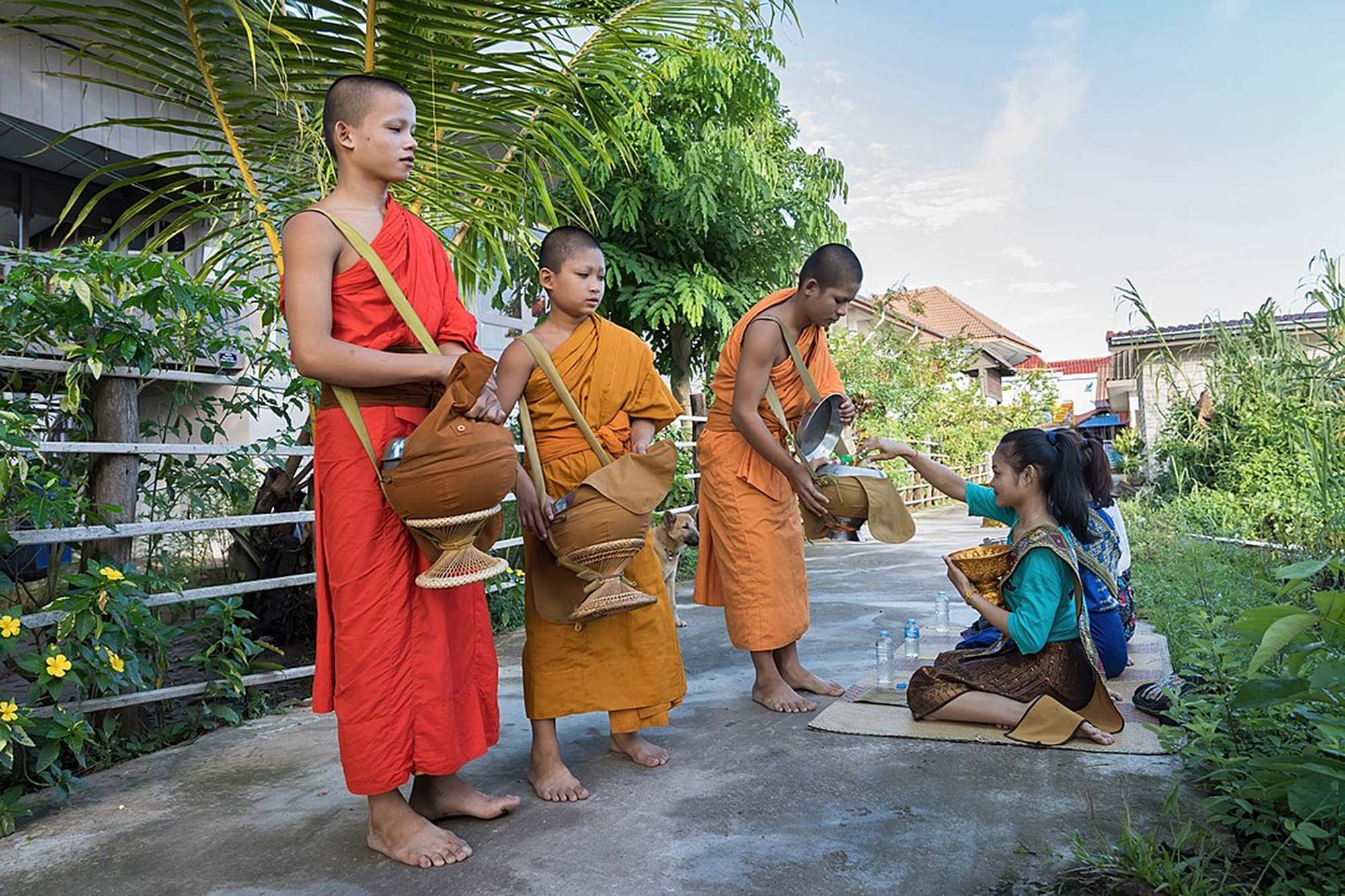 Young monks receiving donations, Si Phan Don, Laos
